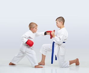 On the simulator little karateka boy is training punch arm