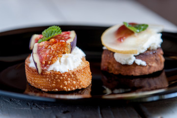 Bruschetta with goat cheese, pear and figs on black plate