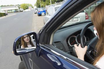 Jugendliche blickt in Seitenspiegel