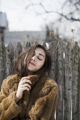 Young woman leaning against wooden fence outdoors
