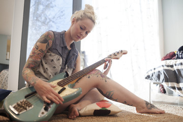 Beautiful young woman playing an electric guitar