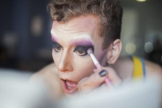 Close up of young man applying drag makeup