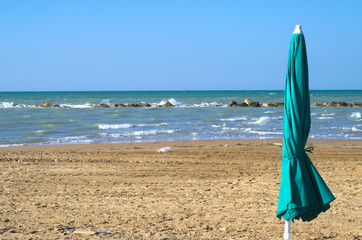 Beach umbrella closed. Sea in the background