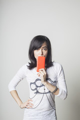 Portrait of woman with smartphone standing against white background