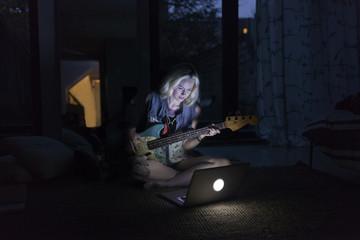 Beautiful young woman playing an electric guitar