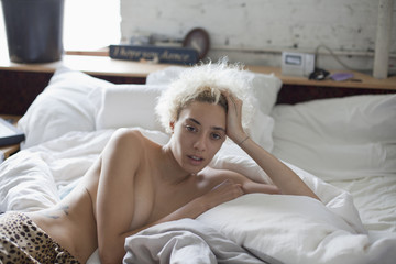 Portrait of shirtless young woman lying on bed