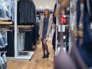 Attractive woman in a boutique fashion dresses from between