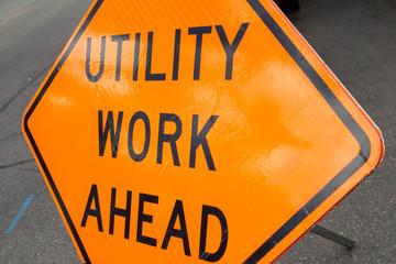 Tilted orange utility work ahead sign