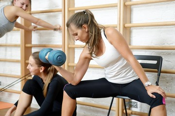 Young woman doing biceps curl exercise with dumbbells in gym