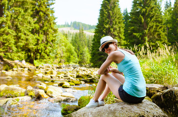 Happy young girl in a nature setting sitting next to a mountain stream.