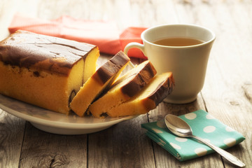 Butter cake with tea cup on wood background