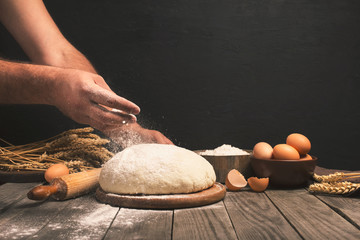 Wall Mural - Men hands sprinkle a dough with flour