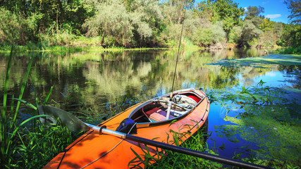 Orange kayak on river with rod on board. Fishing and sport kayaking concept.