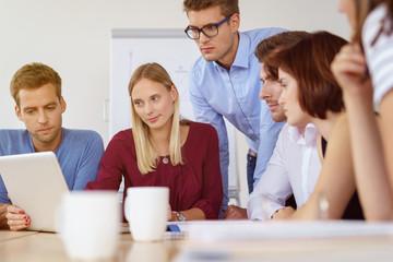 team im büro schaut auf ein tablet mit ernsten gesichtern