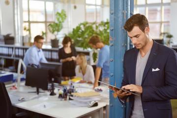 mitarbeiter im büro schaut auf tablet-pc