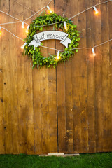 wooden wall and hop wreath with text Just married. Photosession zone