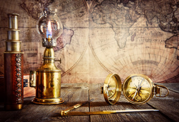 Wall Mural - Exploration and nautical theme grunge background. Compass, telescope, sextant, coin, divider on wood desk.