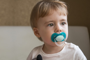 Baby with dummy in his mouth sitting on the bed in the room