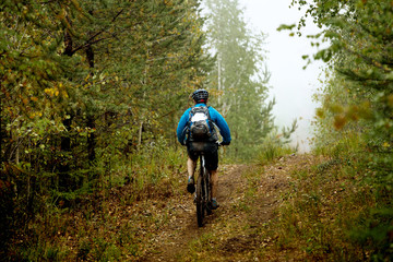 man mountain biking in autumn forest. active and motion lifestyle