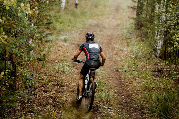 athlete racer mountainbike riding in autumn forest. feet and bicycle wheel in mud