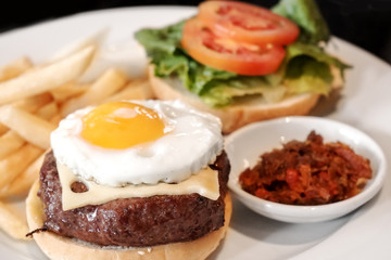 Burger with fried egg, cheese, tomato and vegetable
