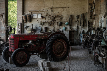 Old tractor in a farmhouse and tools on the wall