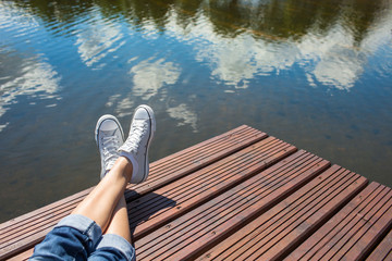 Young girls feet relaxing by a lake.