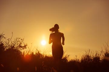 Female runner running at sunset.