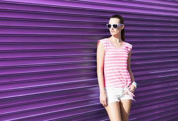 Studio fashion shoot of woman posing against purple background.