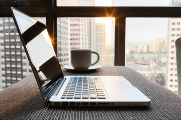 Laptop on office desk early morning.
