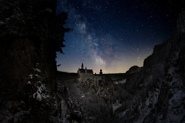 Beautiful night sky star view of world famous Neuschwanstein Castle, Bavaria with the Milky way winter landscape