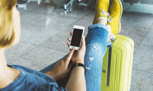 Young hipster girl sitting at airport and put feet in yellow boot on suitcase traveling, female hands using app on making smartphone in terminal area hall, tourist journey trip, mockup blank screen