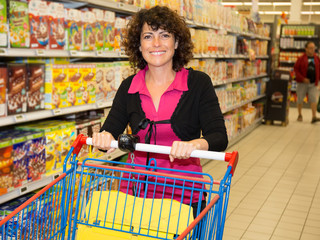 Smiling woman standing with a trolley at a supermarket