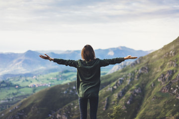 Wall Mural - Happy tourist traveler standing on a rock with raised hands, hiker looking to a valley below in trip in spain, hipster young girl enjoying peak of foggy mountain background landscape view mockup