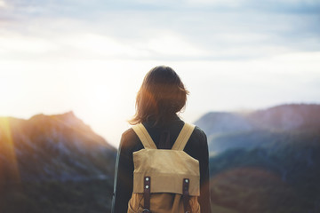 Wall Mural - Hipster young girl with bright backpack enjoying sunset on peak of foggy mountain. Tourist traveler on background valley landscape view mockup. Hiker looking sunlight flare in trip in northern spain
