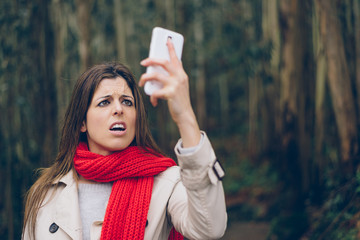 Upset woman looking worried about losing mobile or gps signal coverage on smartphone. Brunette girl in trouble or receiving bad news during autumn trip.