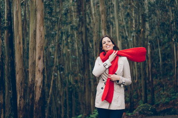 Young woman wearing autumn fashion clothes during trip to the forest. Brunette model enjoying weeked leisure in raincoat, red rain boots and knitted scarf.