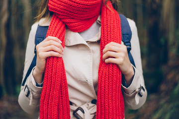 Autumn warm fashion clothes. Detail of woman wearing red knitted scarf and raincoat. Wall mural