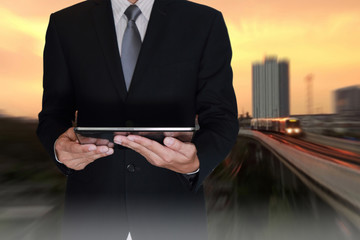 Business man hand hold tablet on camera zoom abstract electric train and sunlight of sunset background as telecommunication and transportation concept.