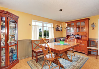 Traditional dining area with wooden furniture and rug.