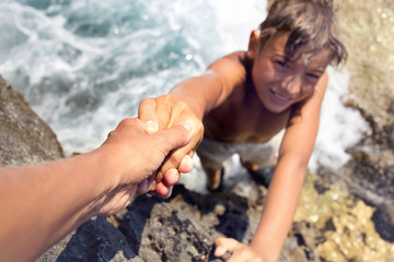 boy helped by a friend to climb an inaccessible cliff