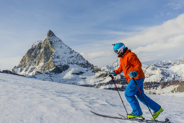 Ski touring man reaching the top in Swiss Alps. Matterhorn in th