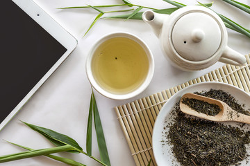 tablet computer, teapot and cup of herbal green tea on bamboo with white table background. over light