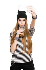 Cute teenage girl drinking coffee taking a selfie on smart phone
