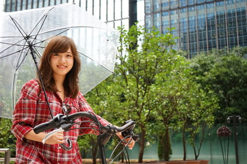 Young Japanese woman riding on a bike in a rainy weather