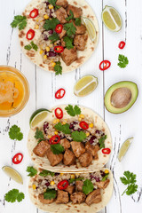 Mexican tacos with quinoa salad, meat, black beans and corn on rustic wooden table. Recipe for Cinco de Mayo party. Top view.