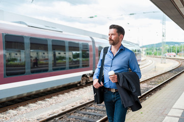 Mature businessman with takeaway coffee walking along on railway platform