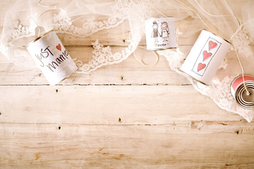 Lace and just married cans on wooden background