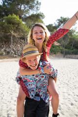 Man on beach giving smiling woman piggyback, Majorca, Spain