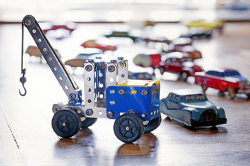 Tow truck toy and other little cars on the floor. Selective focus on the truck.
